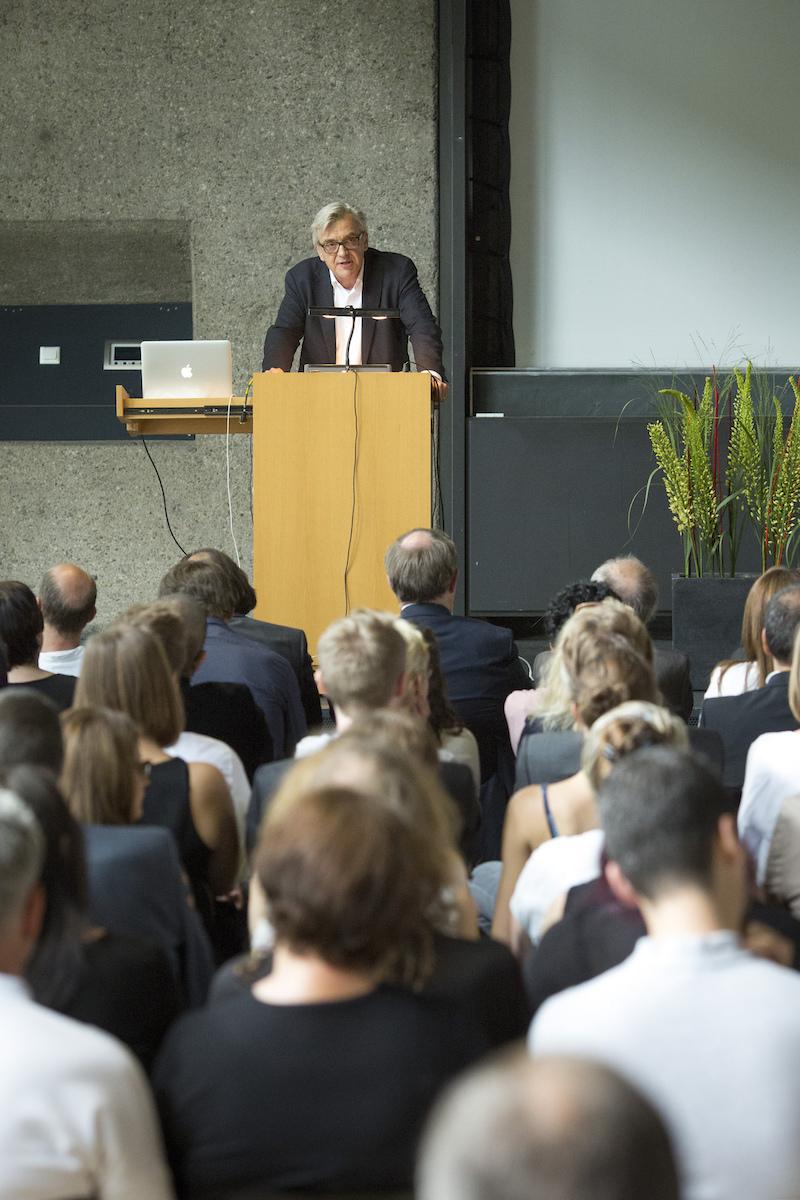 Uwe Schröder steht am Podest auf der Bühne des Karl-Schüssler-Saals